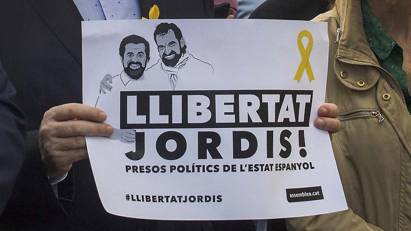 Cartell en què s'exigeix la llibertat de Jordi Sànchez i Jordi Cuixart durant una manifestació.