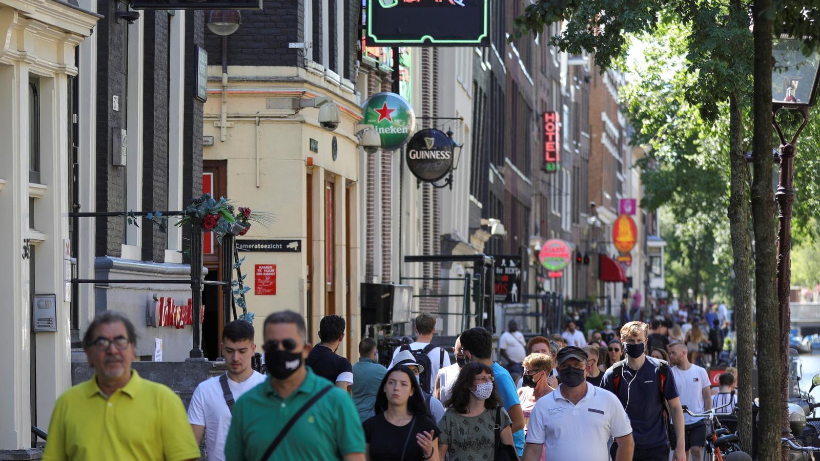 Gent amb mascareta pels carrers d'Amsterdam.