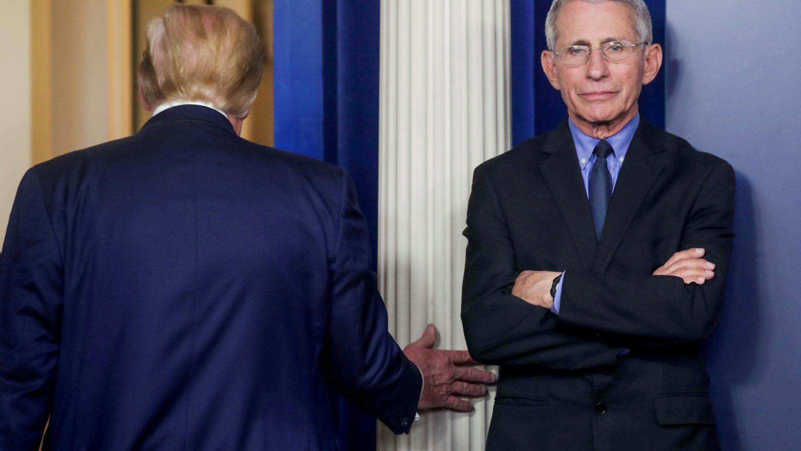 Trump sortint de la sala de premsa  passa per davant d'Anthony Fauci, cap del comitè de crisi pel coronavirus
