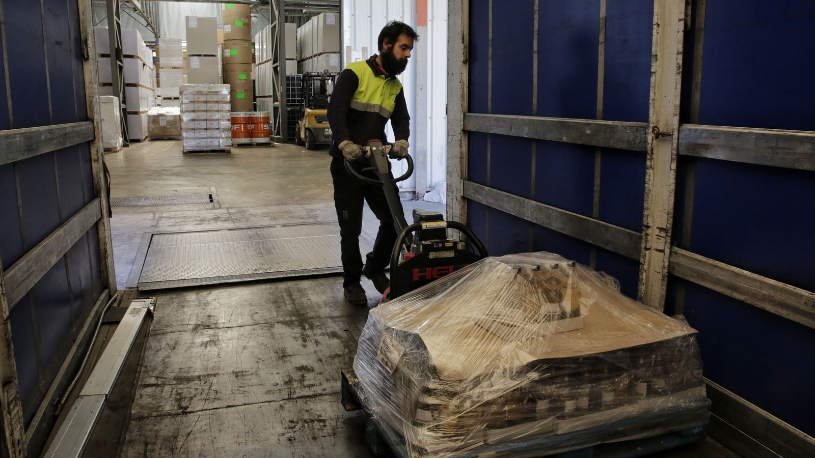 Un treballador de l'empresa Mestrans carrega un camió en un polígon industrial d'Igualada