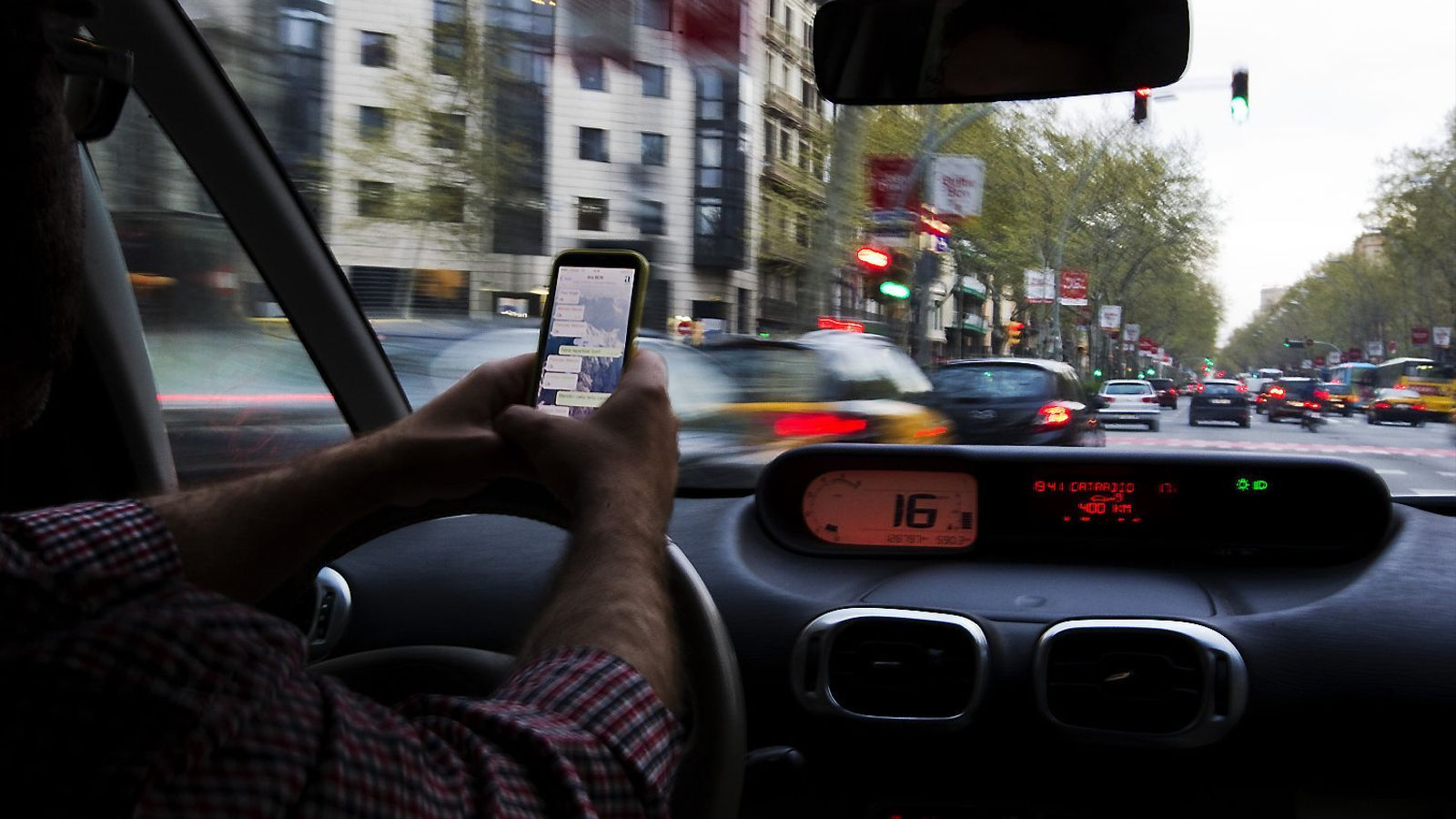 Un conductor fent servir un telèfon mòbil mentre circula per un carrer de Barcelona.