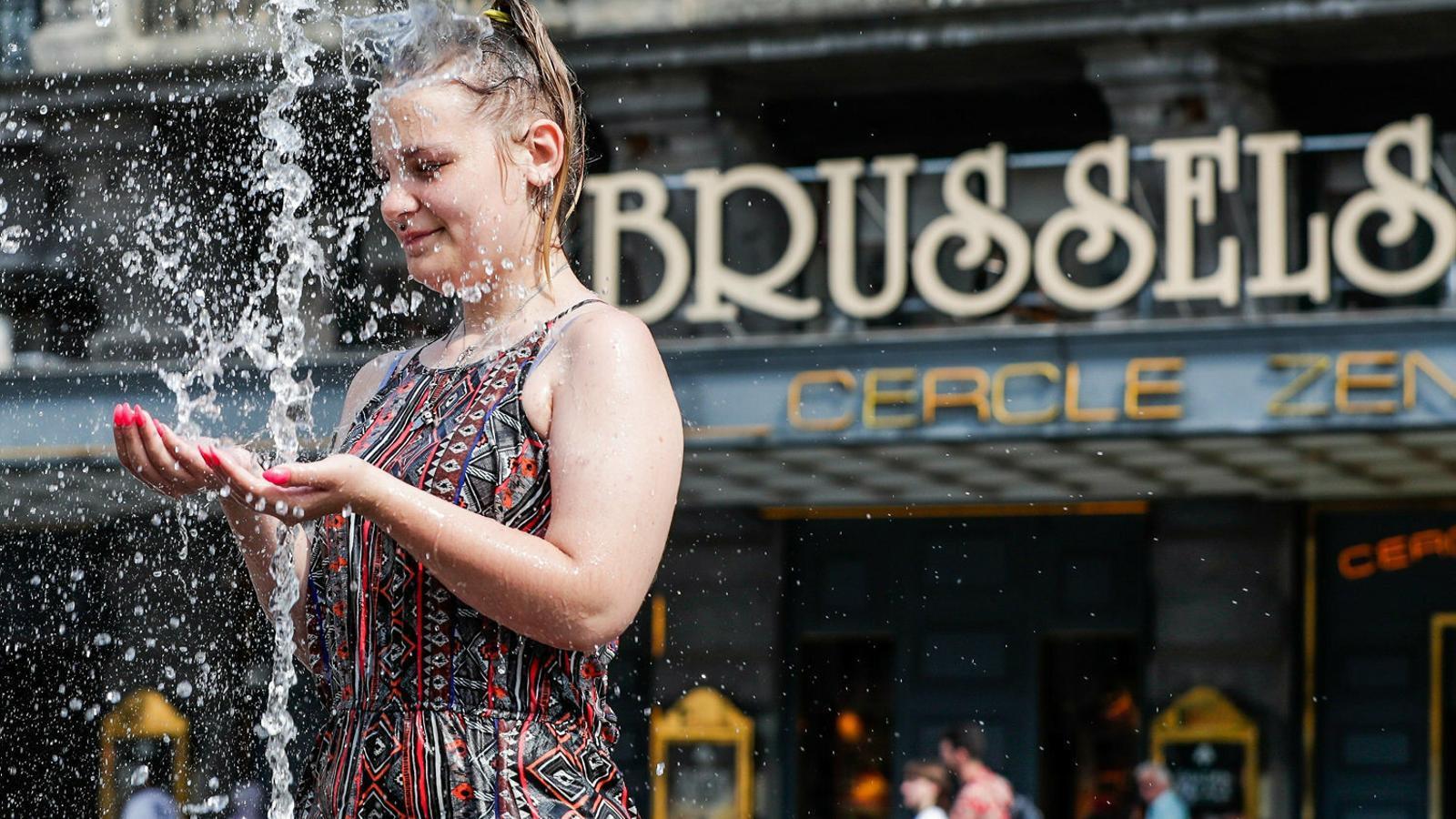 Una noia refrescant-se en una font pública d'una plaça de Brussel·les, a Bèlgica, on aquesta setmana s'han batut els rècords històrics de temperatura màxima a causa de la forta onada de calor que s'ha escampat per bona part d'Europa.