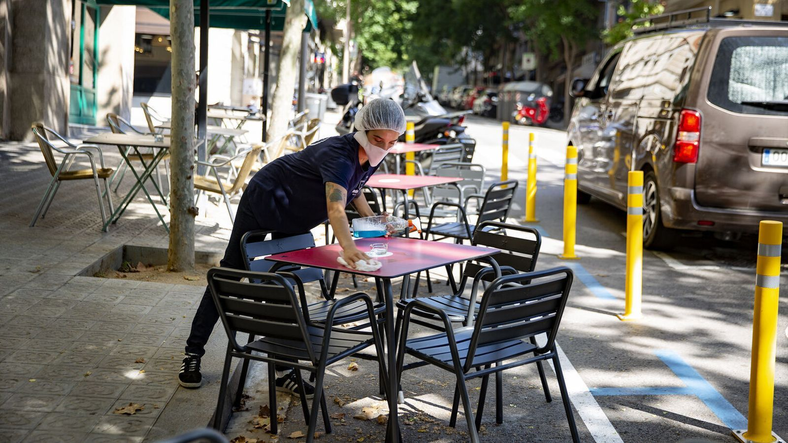 Una cambrera recollint la taula de la terrassa d'un bar de Barcelona durant la pandèmia del covid-19