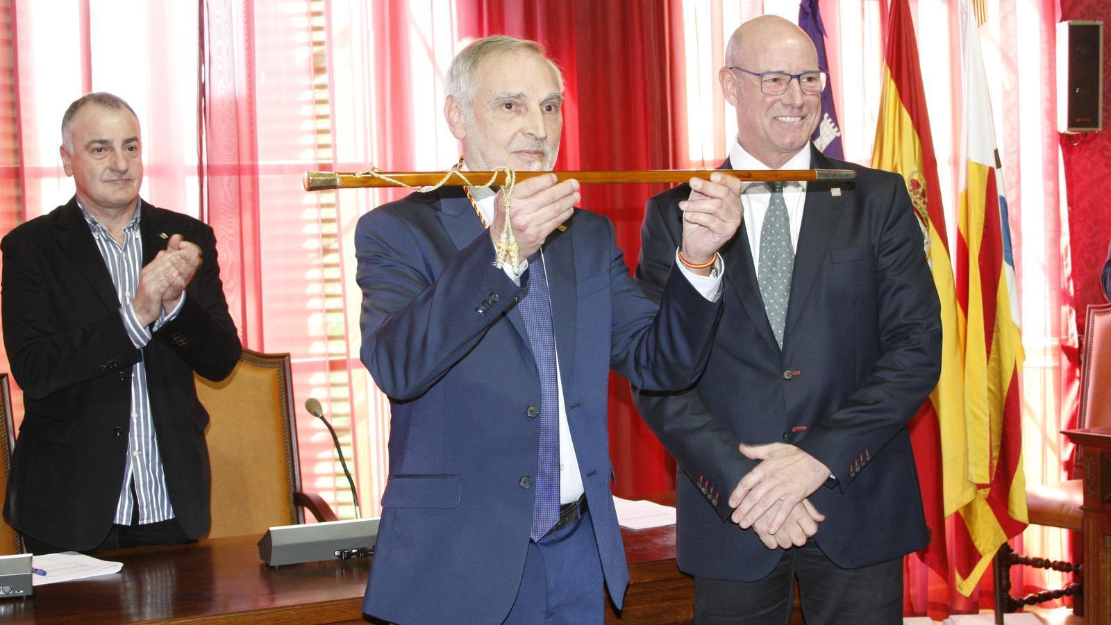 Gori Estarellas, després de rebre la vara de mans del seu antecessor, Bernardí Vives (dreta), mentre Jaume Tomàs (MÉS) aplaudeix..