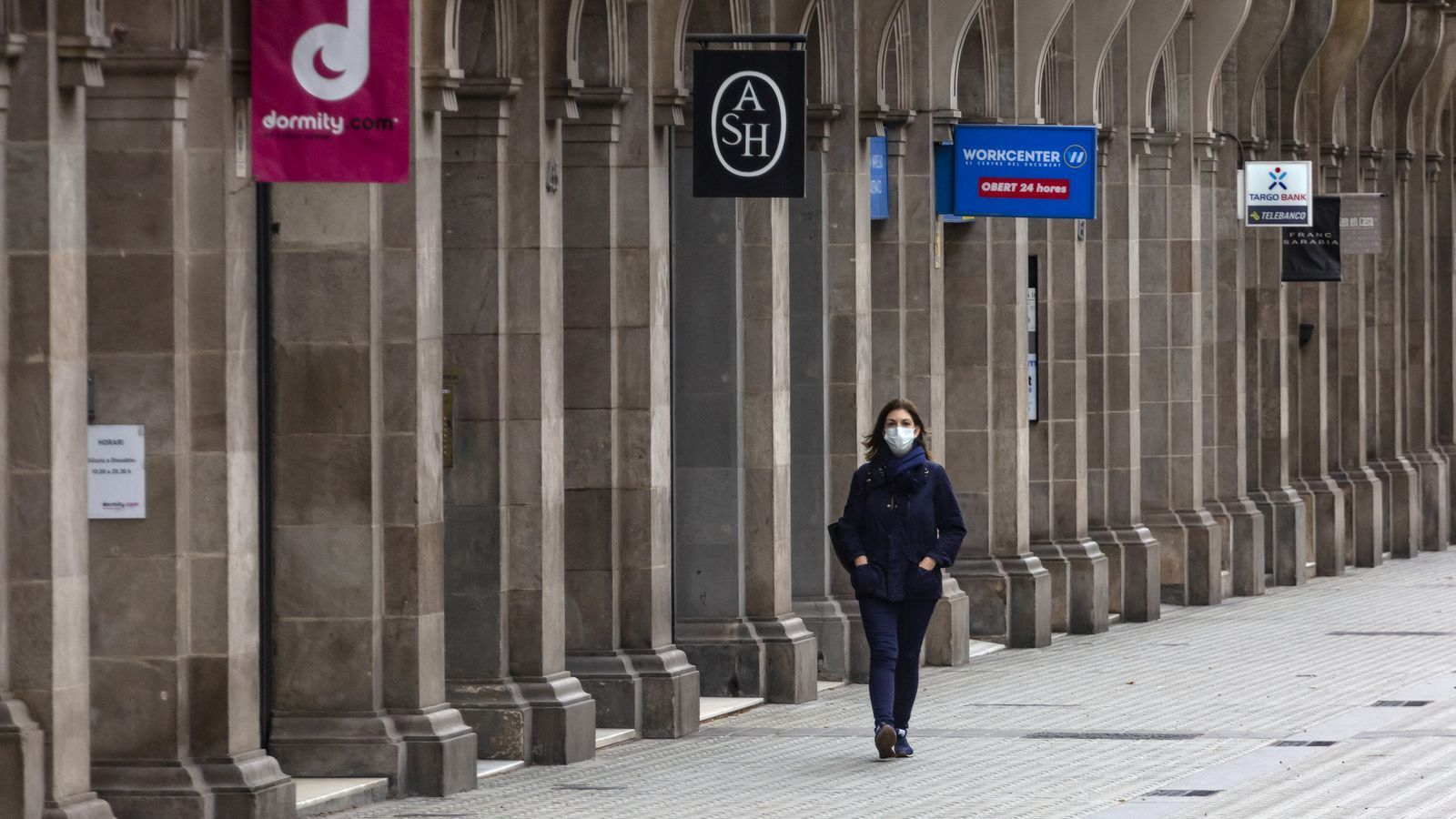 Una dona passeja per davant de les botigues tancades a la Diagonal de Barcelona.