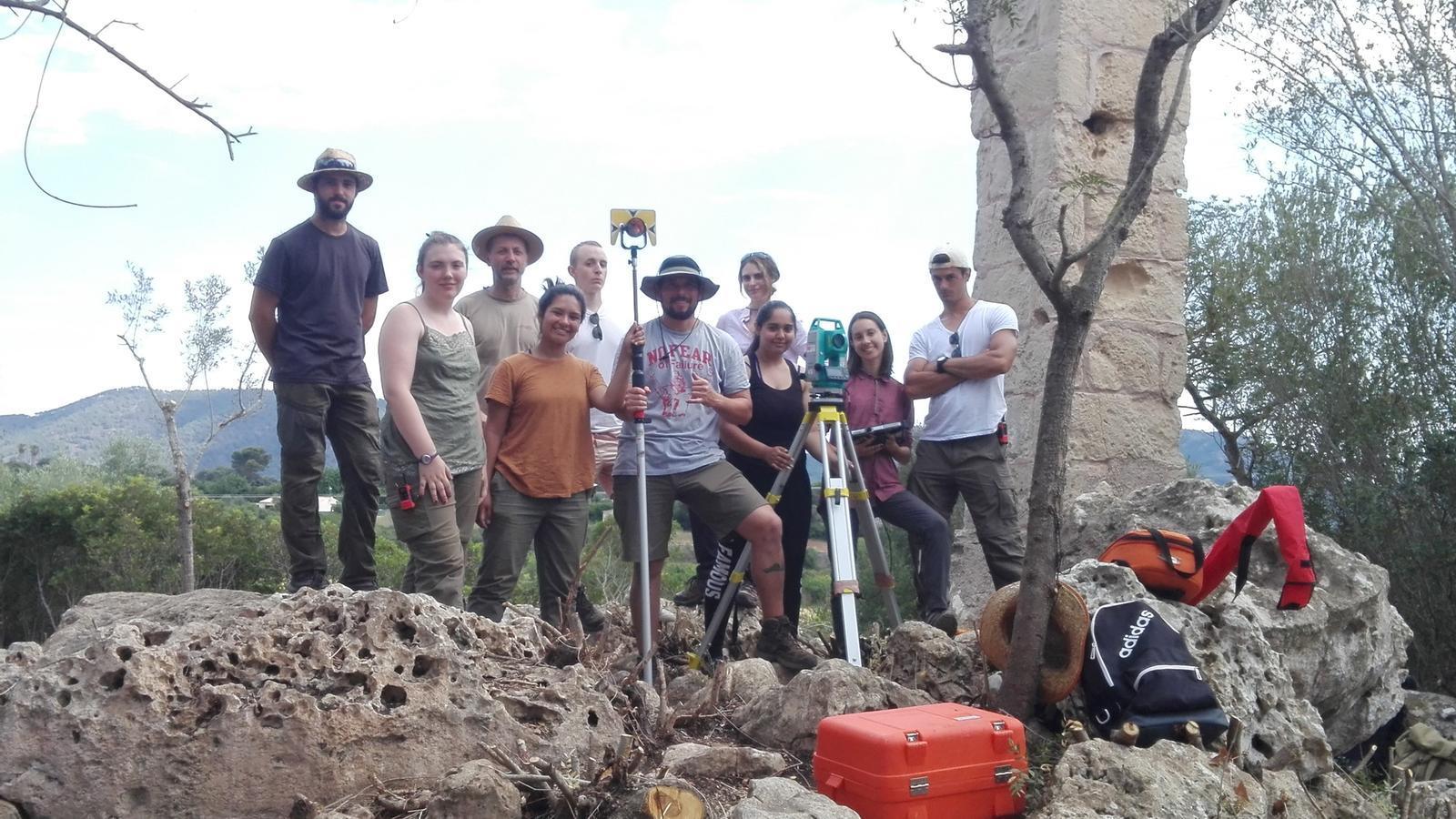 Estudiants d'arqueologia i professors sobre part de les restes descobertes.