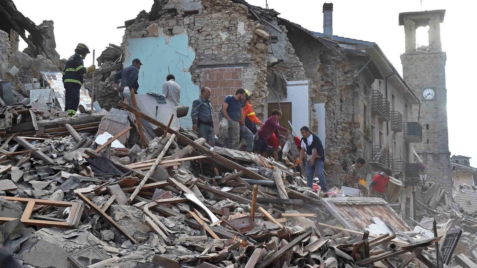 Bombers i voluntaris ajudant en les tasques de rescat de les persones atrapades en les runes del terratrèmol que va sacsejar Amatrice ahir.