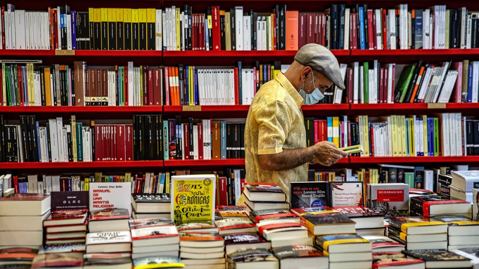 Un client remenant llibres a la llibreria Documenta de Barcelona el 23 de juliol, el Dia del Llibre i la Rosa.