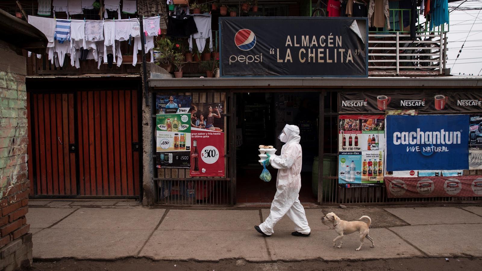 Una veïna de la comuna de Renca a Santiago, Xile, es prepara per lliurar dinars a domicili a famílies contagiades amb la COVID-19.