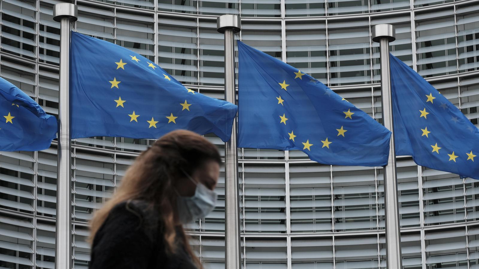 Una dona amb mascareta davant les banderes de la Unió Europea alçades davant la seu de la Comissió Europea a Brussel·les