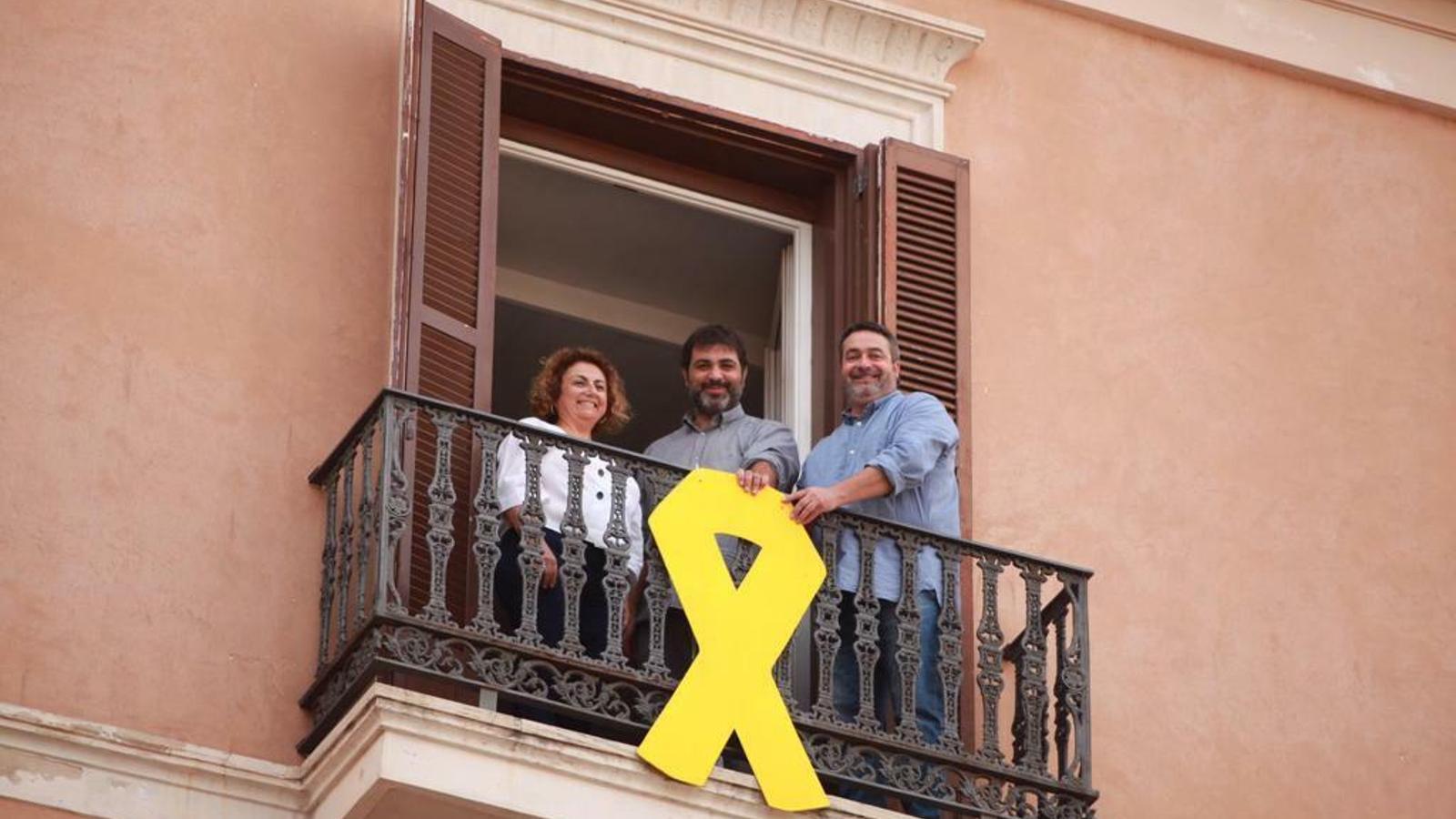 Imatge dels disputats de MÉS penjant el llaç groc a la façana del Parlament. / MÉS PER MALLORCA