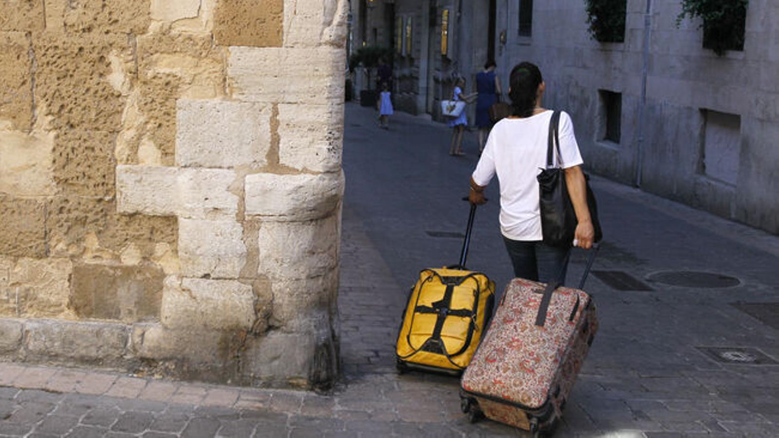 Una dona amb les seves maletes de viatge pels carrers de Palma.