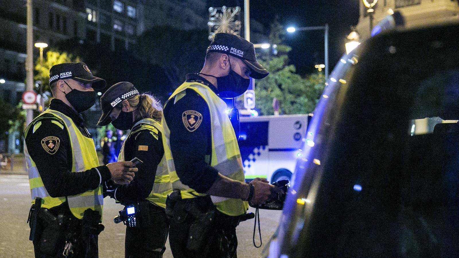 Tres agents de la Guàrdia Urbana de Barcelona durant un control pel toc de queda