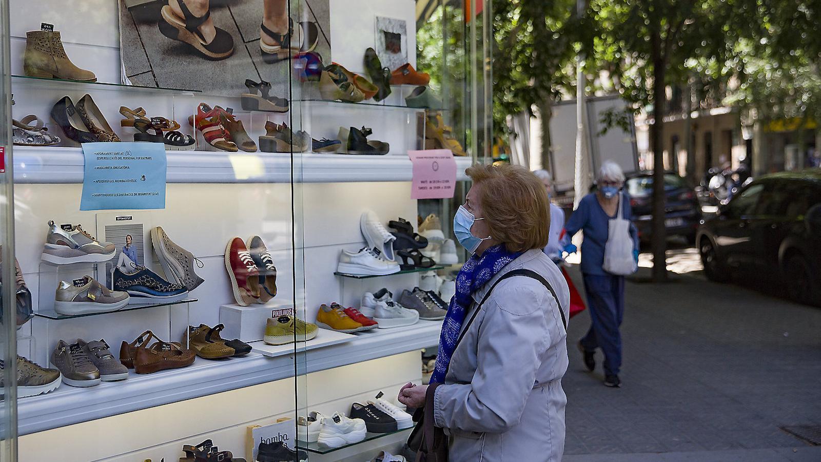 Una dona mirant l'aparador d'una botiga de Barcelona quan la ciutat era en fase 0,5.