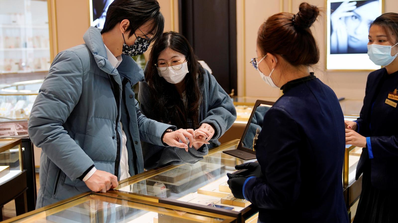 Una parella de Xangai no ha volgut faltar al ritual de Sant Valentí tot i l'epidèmia, i observa com una venedora d'un centre comercial de la ciutat els mostra un collaret