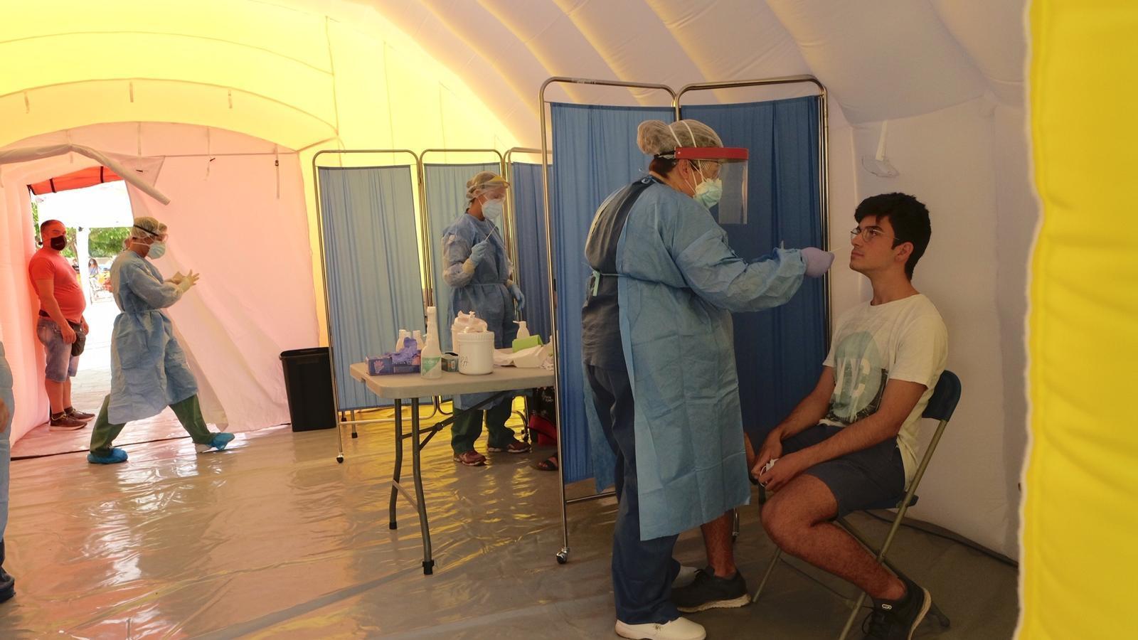 Una infermera extreu una mostra a un jove per fer-li la PCR a l'interior d'una de les carpes de Salut instal·lades a Terrassa aquest divendres.