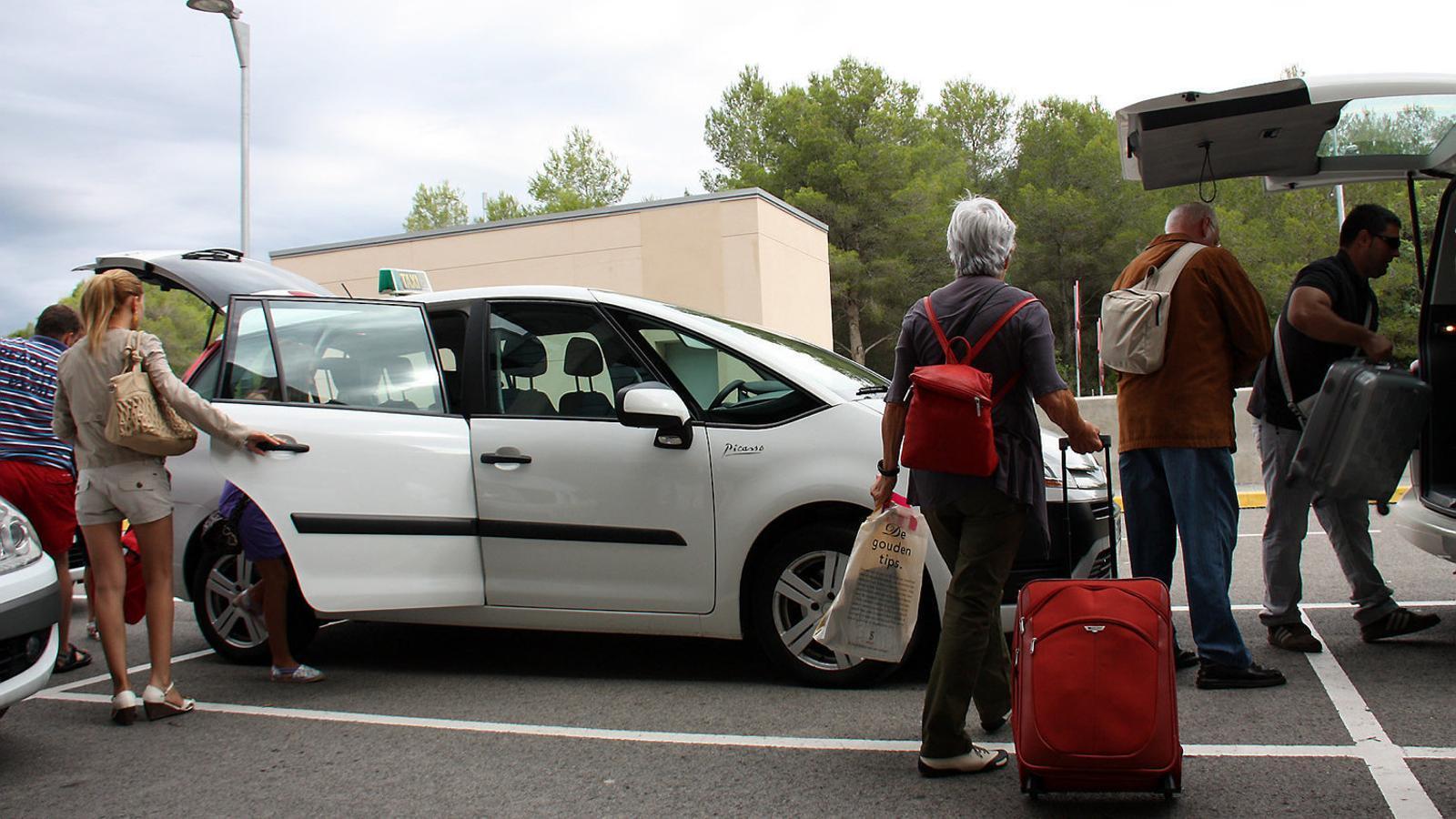 Passatgers de l'estació de l'AVE del Camp de Tarragona agafant  un taxi.