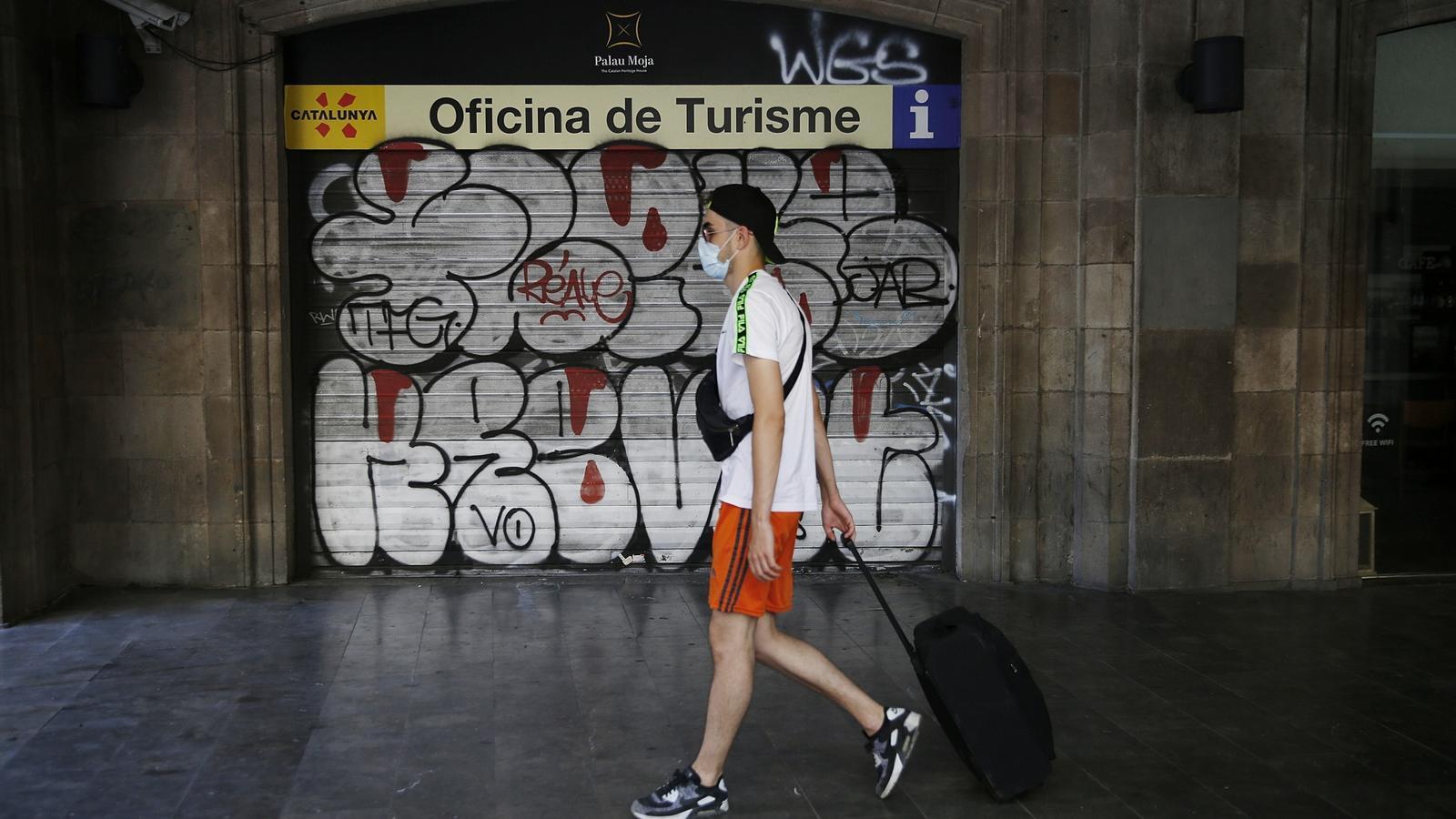 Un turista passa per davant de l'oficina d'informació del palau Moja,  tancada