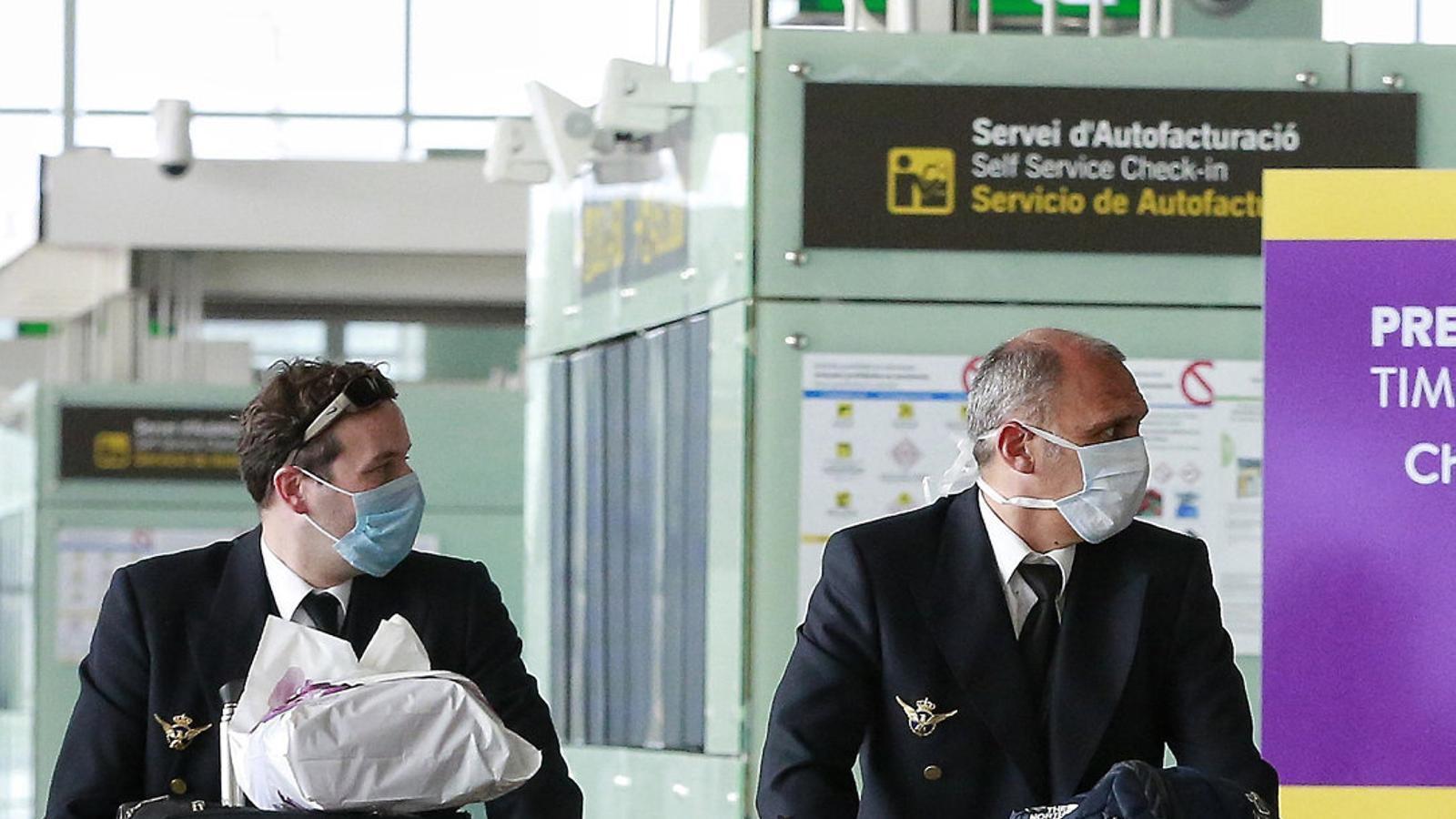 Dos pilots circulant amb mascareta per l'aeroport  Del Prat, pràcticament desert, durant la pandèmia del coronavirus.