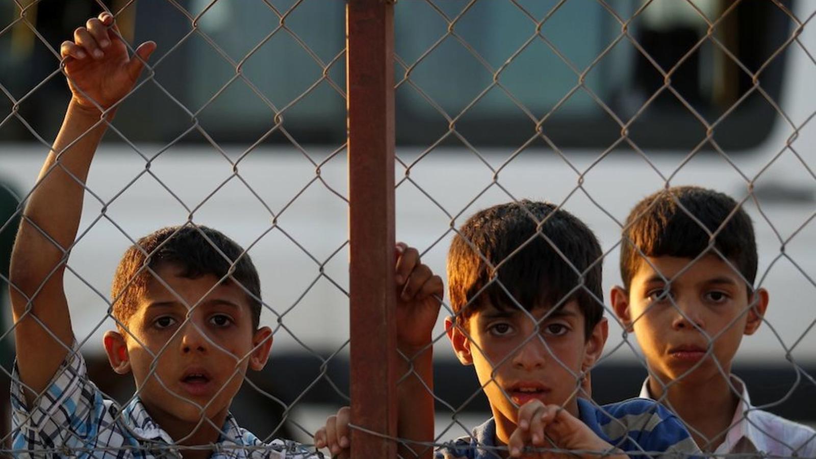 Uns joves refugiats sirians miren a fora des del camp de Reyhanli, a Turquia. Reuters