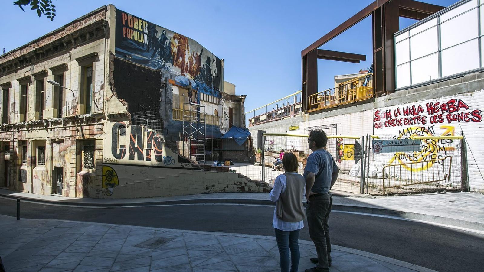 Dos veïns observant les obres de reconstrucció de Can Vies el maig del 2015.