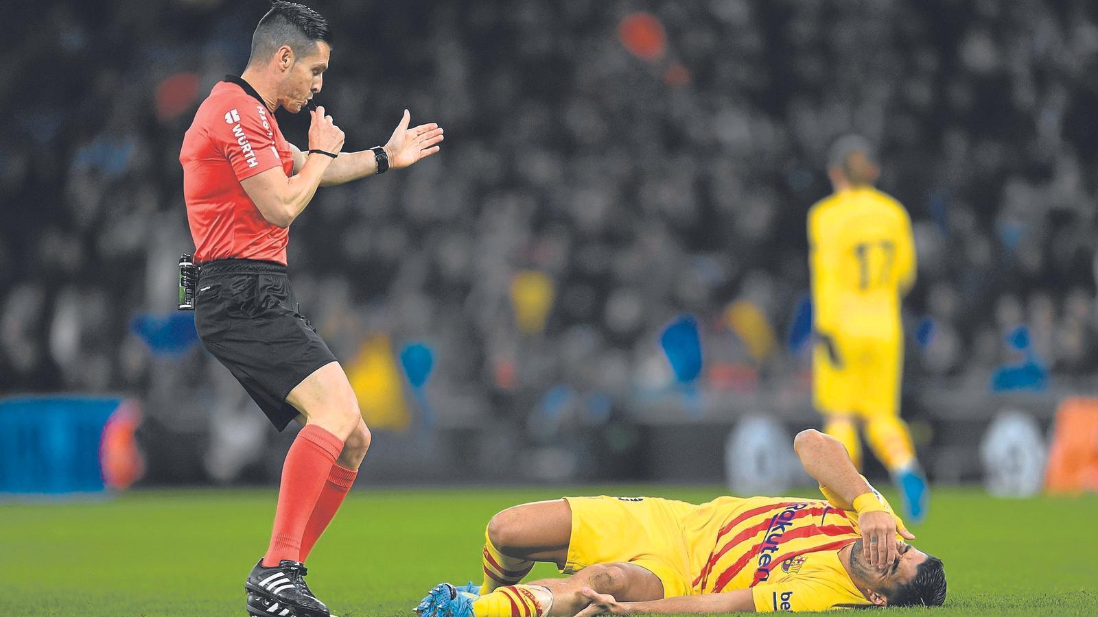 Luis Suárez, estirat al terra després de rebre una entrada en el derbi contra l'Espanyol