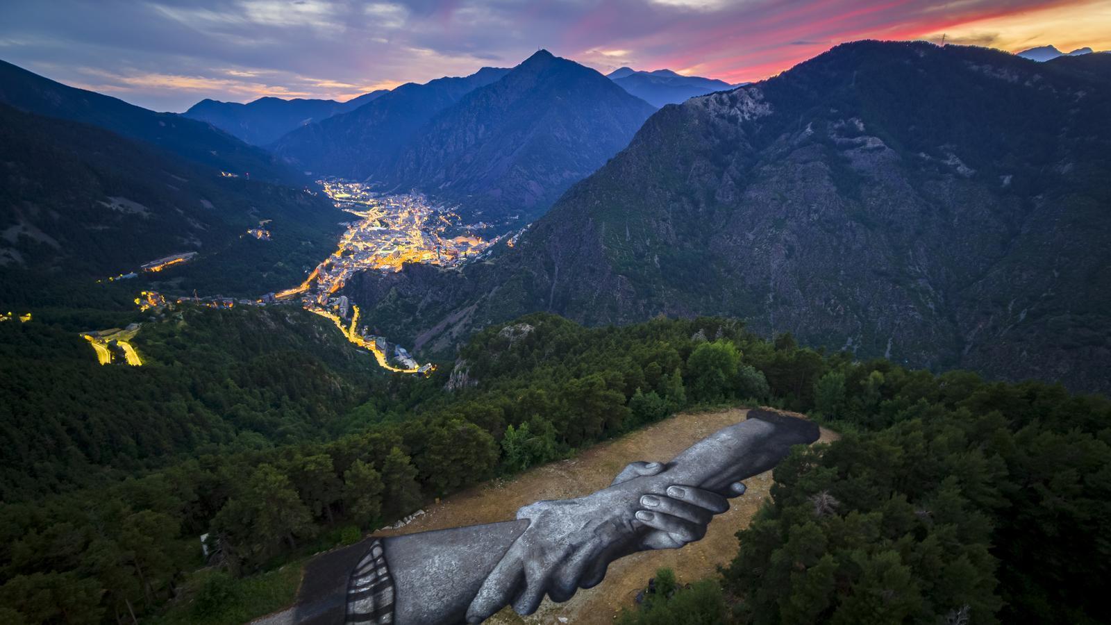 Primer pla de l'obra amb el fons de la ciutat d'Andorra la Vella. / BEYOND WALLS PROJECT