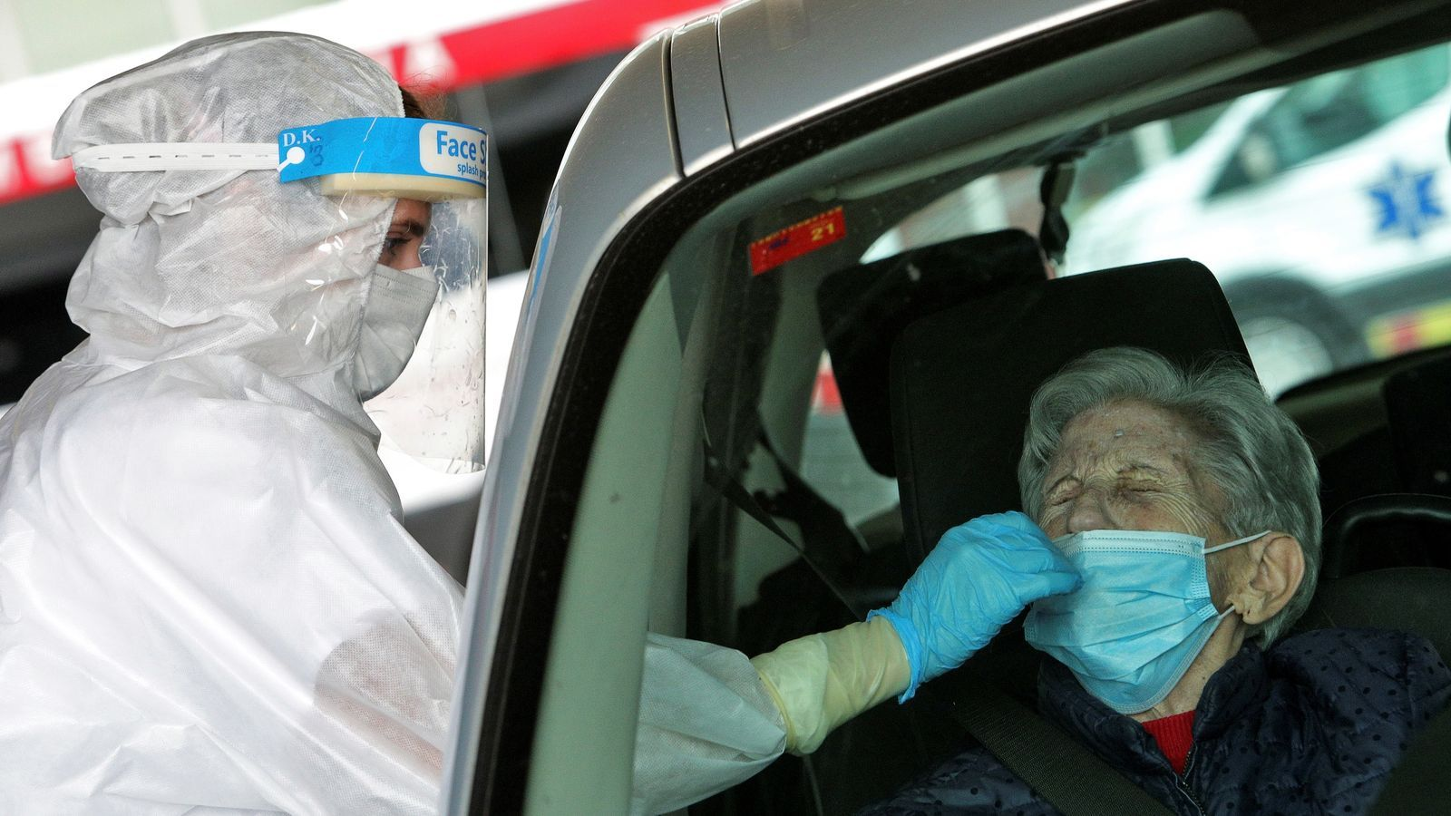Una sanitària pren una mostra per a una prova PCR a les portes de l'hospital de Gandia