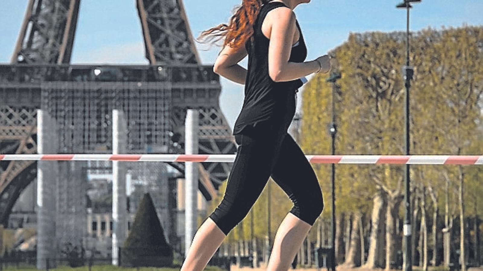 Una jove corrent per davant de la Torre Eiffel de París