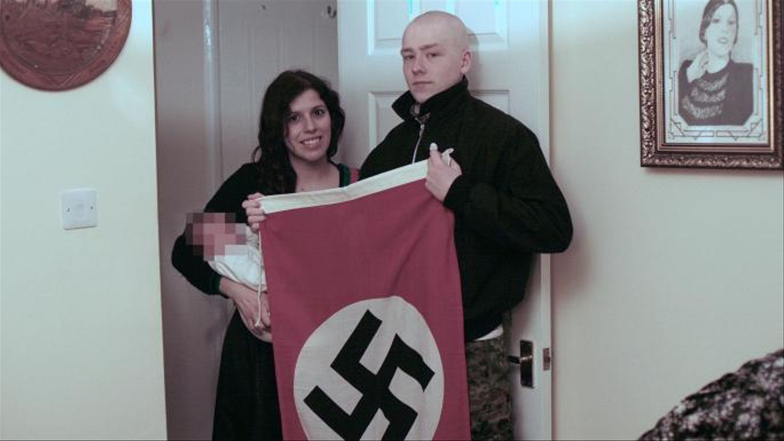 Els dos joves amb la criatura mostrant una bandera nazi