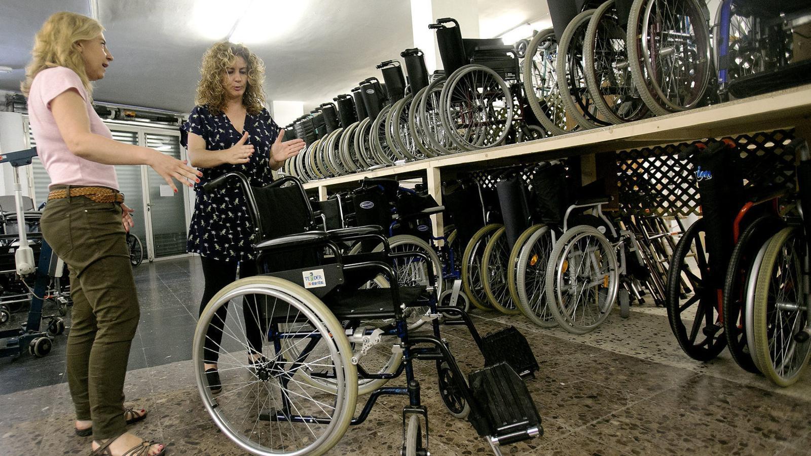La terapeuta ocupacional explicant les característiques tècniques d'una cadira de rodes a una usuària.