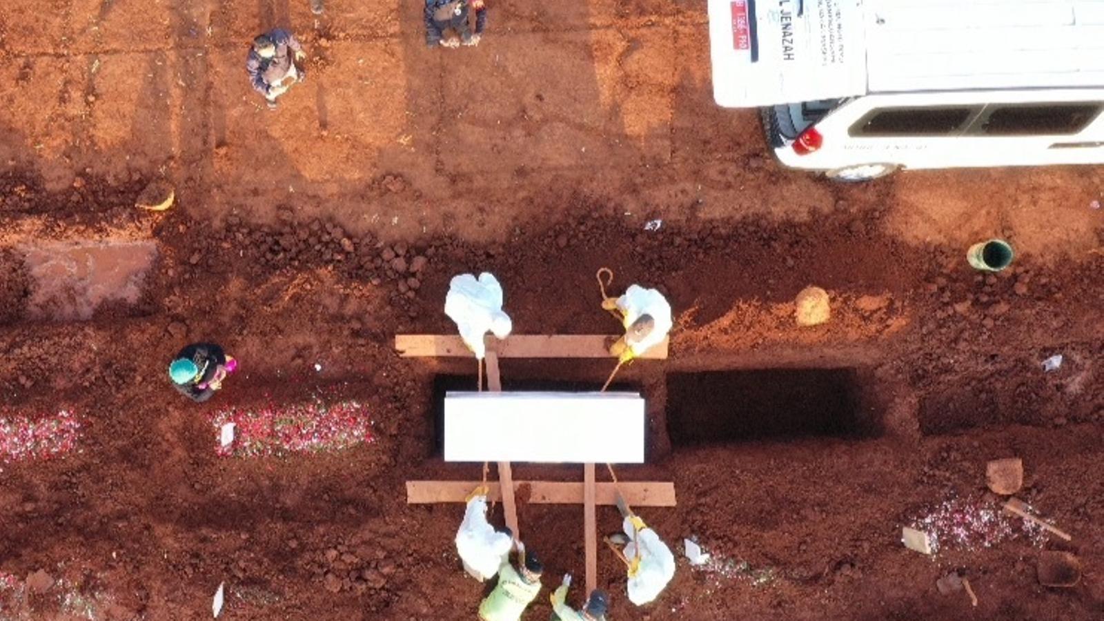 Operaris enterren el cos d'una víctima del covid-19 en un cementiri de Jakarta, la capital d'Indonèsia