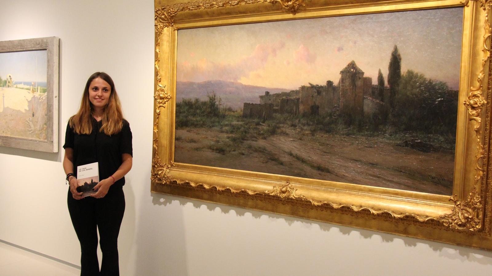 Mireia Moya davant de 'Paisatges', l'obra que la va inspirar a escriure el relat de misteri./ N. T - T. N.