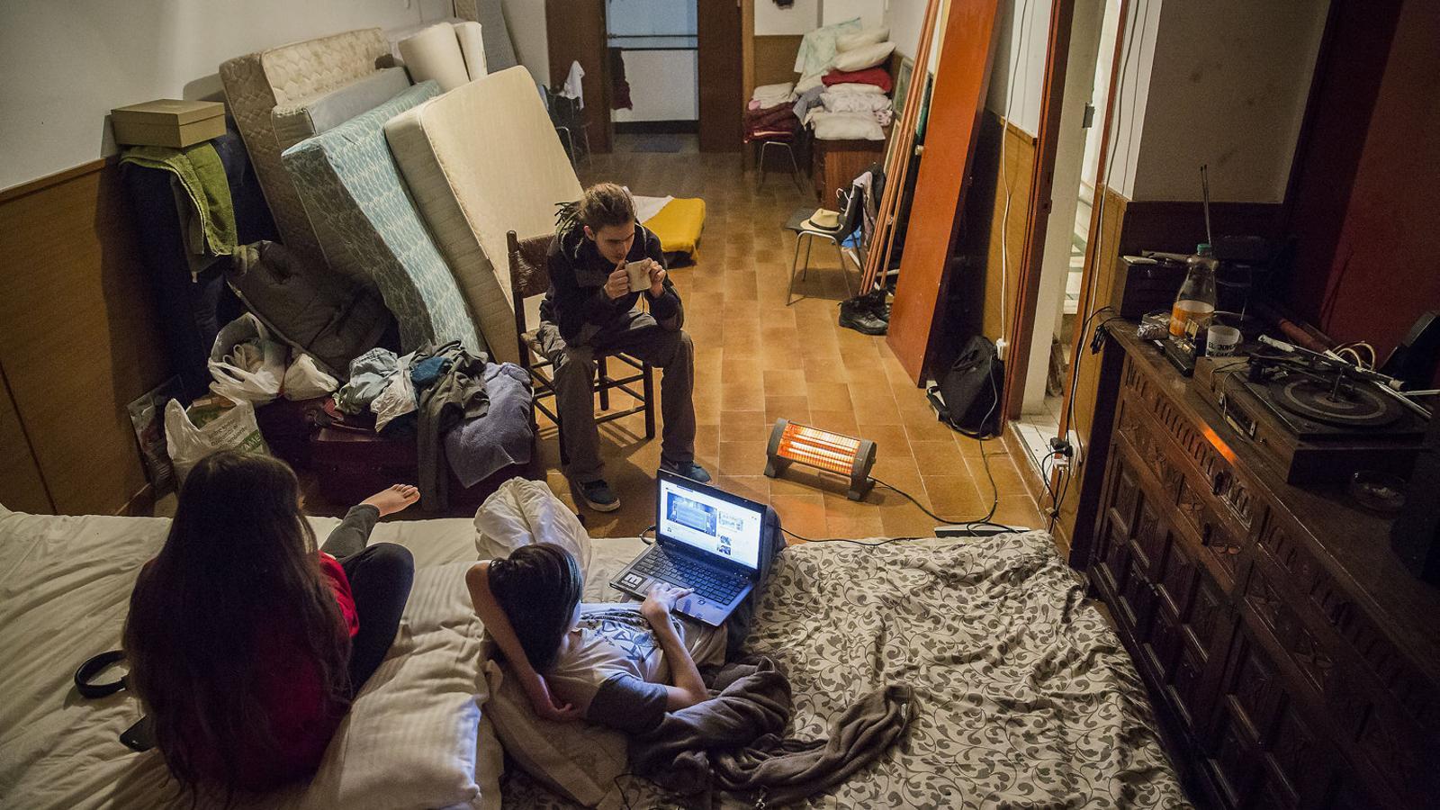 El Mark i la Miroslava, d'esquena als llits, i l'Aleksander, de cara, fills de la família ucraïnesa que viu a l'espai ocupat Casa Cadis.