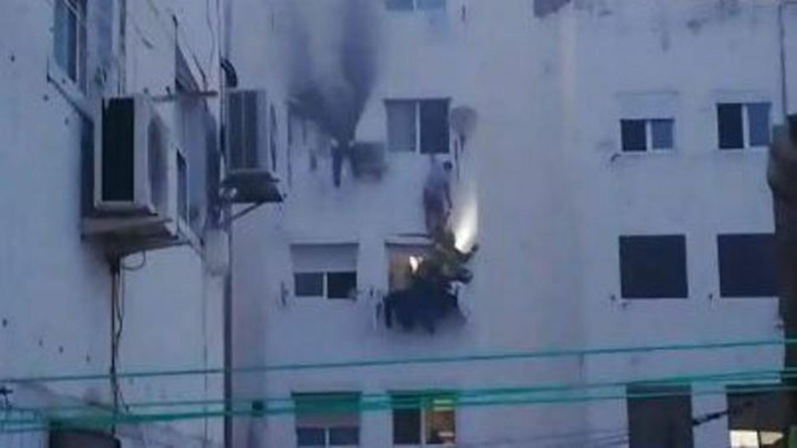 Moment, capturat per un veí, en que els bombers rescaten una de les persones quan intentava fugir pel celobert