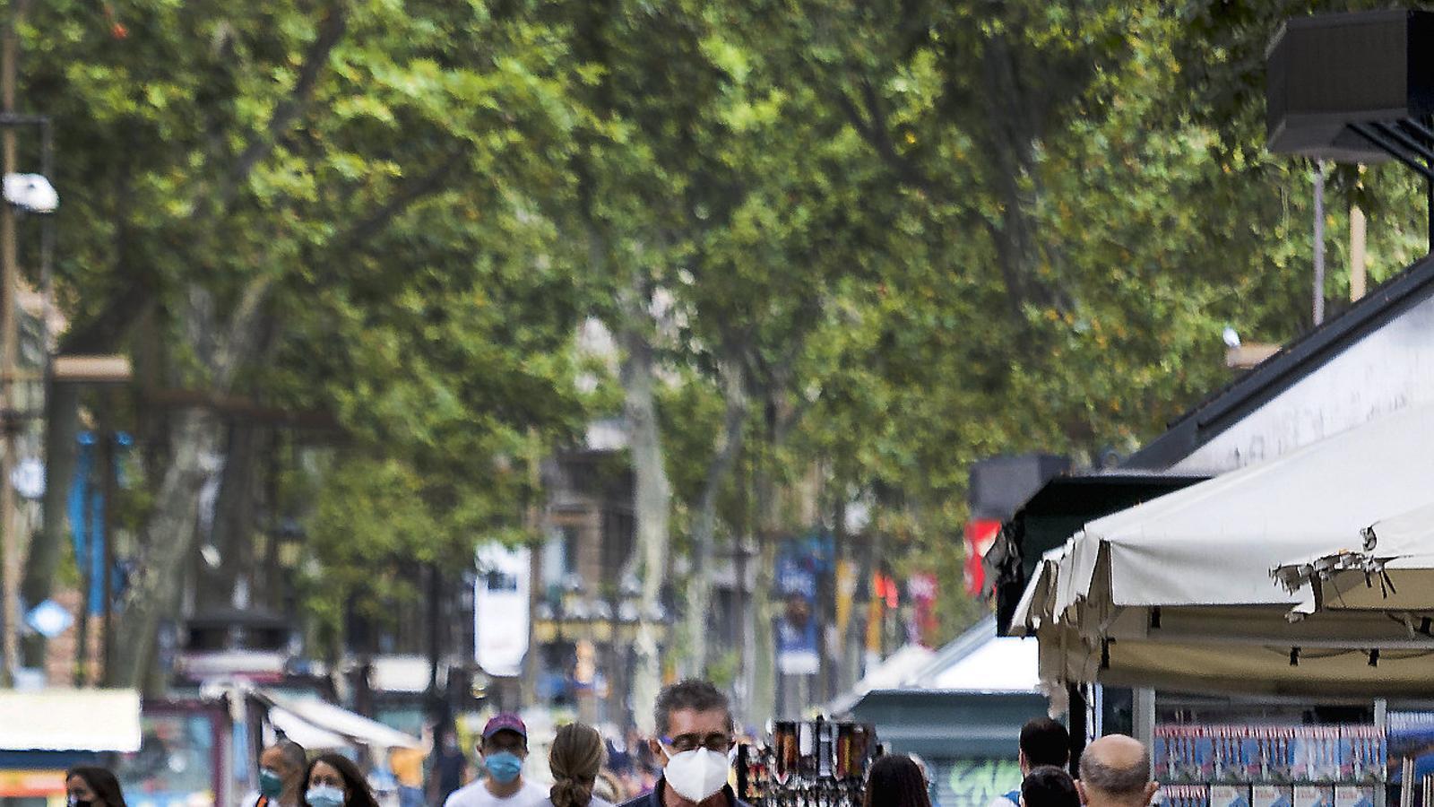 Diverses persones amb mascareta, una de les mesures per la pandèmia del covid-19, passejant per la Rambla de Barcelona en una imatge recent.