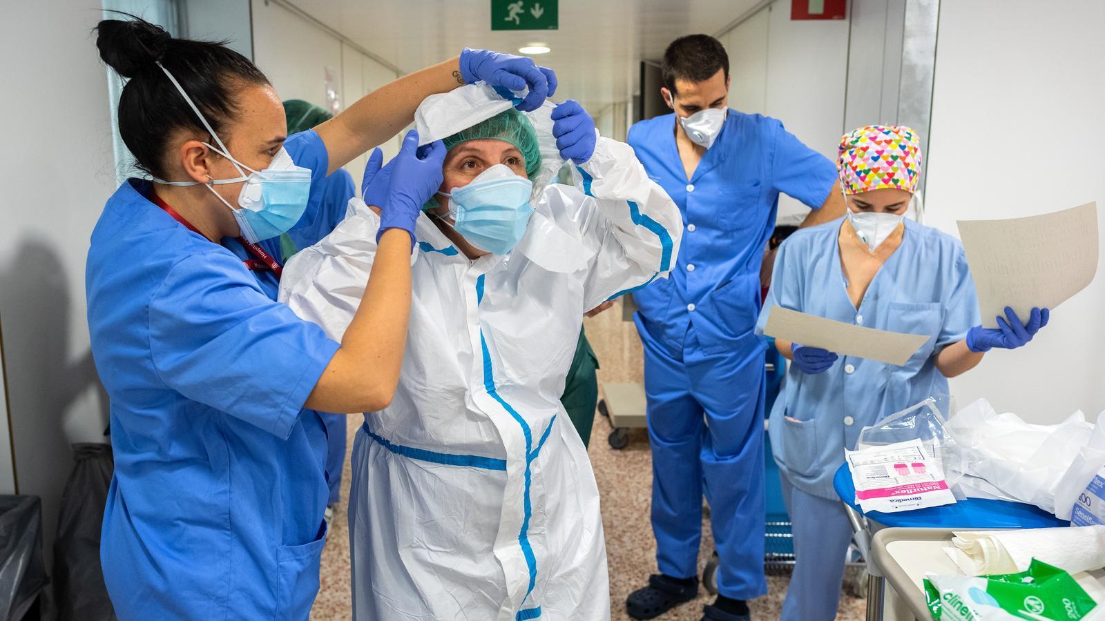 Una infermera ajuda a la doctora Mari Paz Fuset a posar-se l'equip de protecció a l'Hospital Universitari de Bellvitge