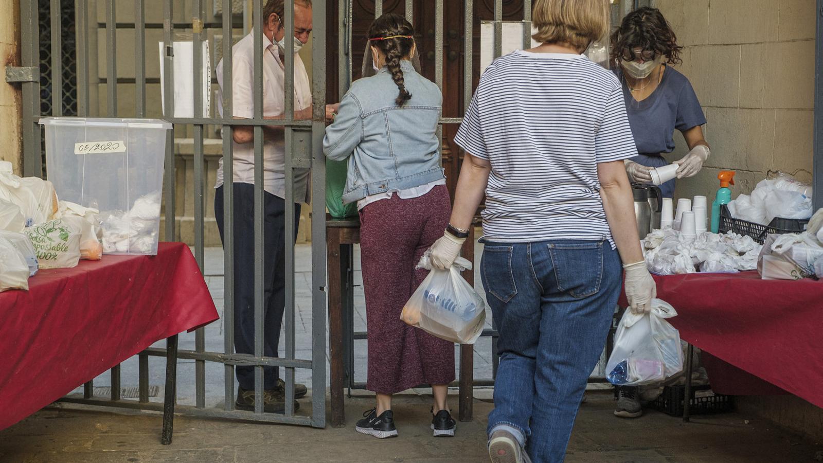 Cues en una parròquia de persones recollint bosses d'aliments. / MANOLO GARCÍA