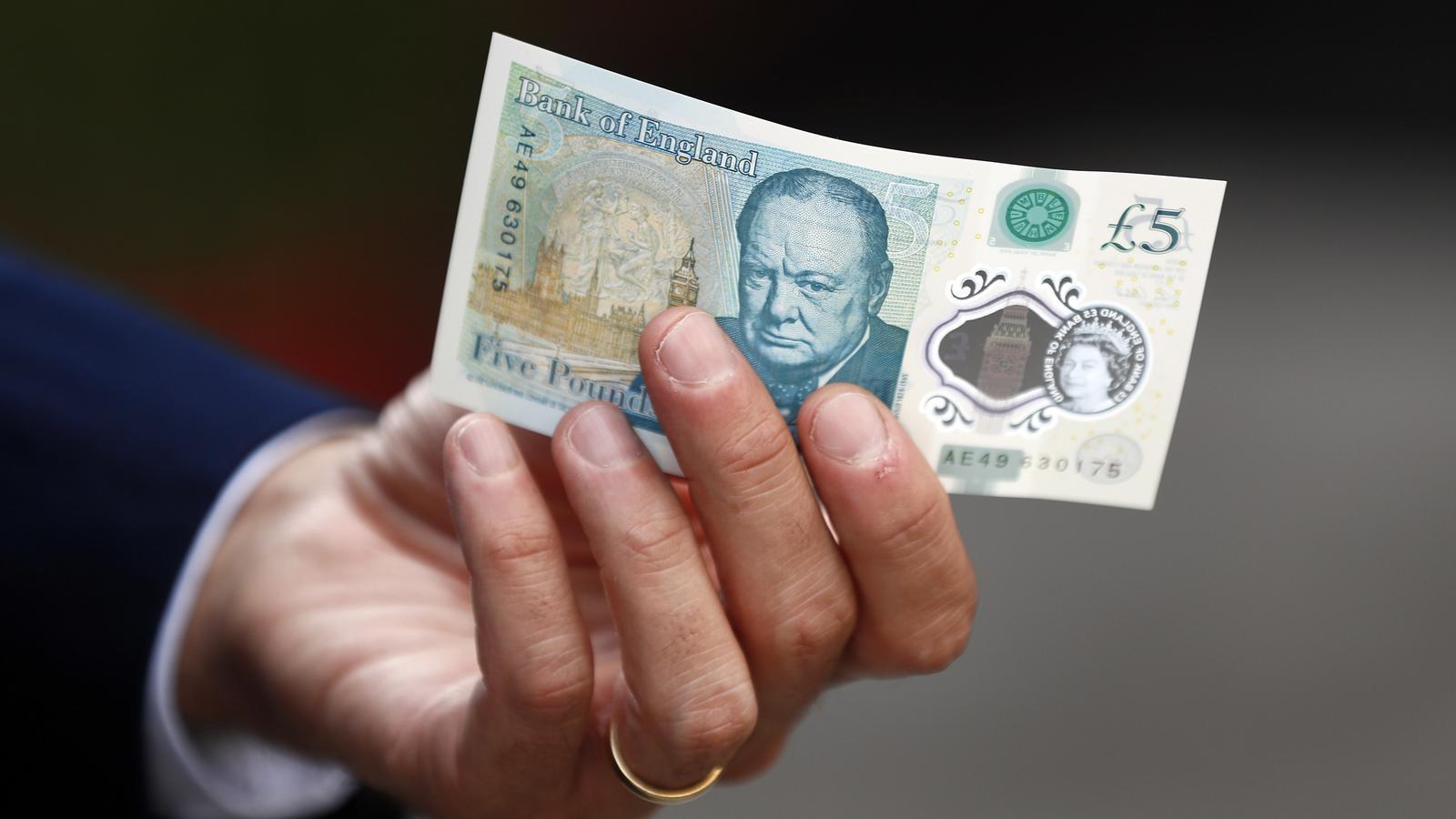 El governador del Banc d'Anglaterra mostra els nous bitllets de cinc lliures amb el rostre de Churchill.