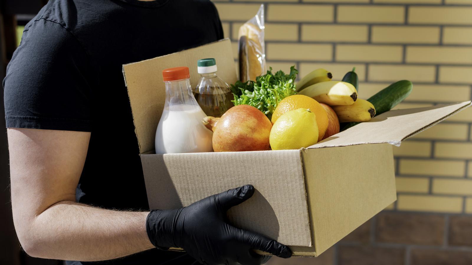 Un home carregant una caixa d'aliments frescos i llet
