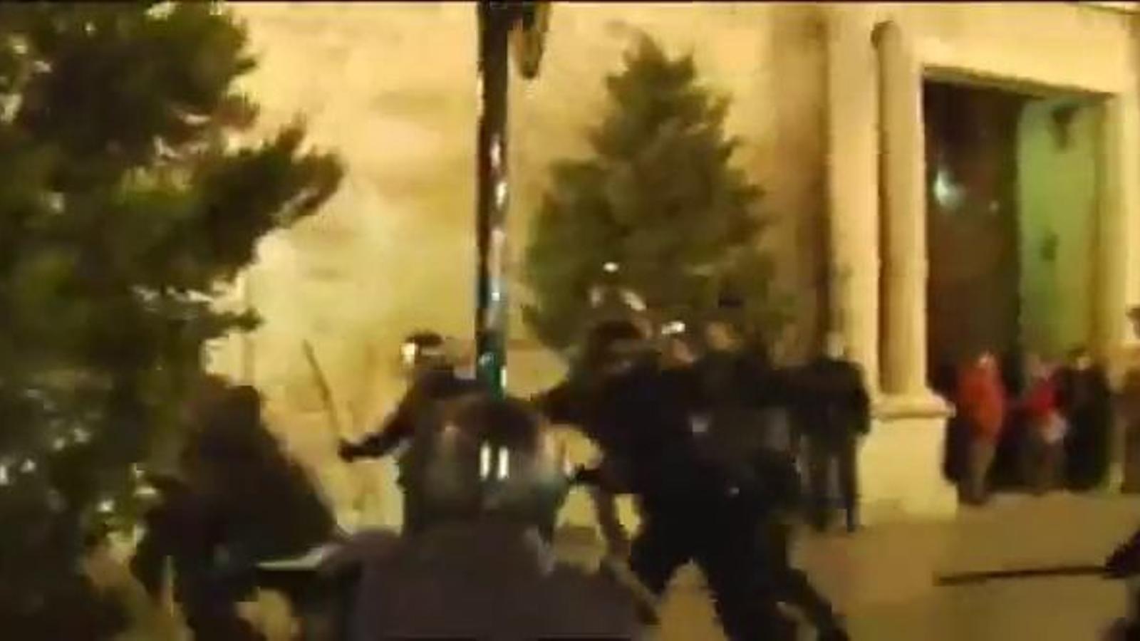 Un policia empeny dues noies cap a un cotxe durant les càrregues a València