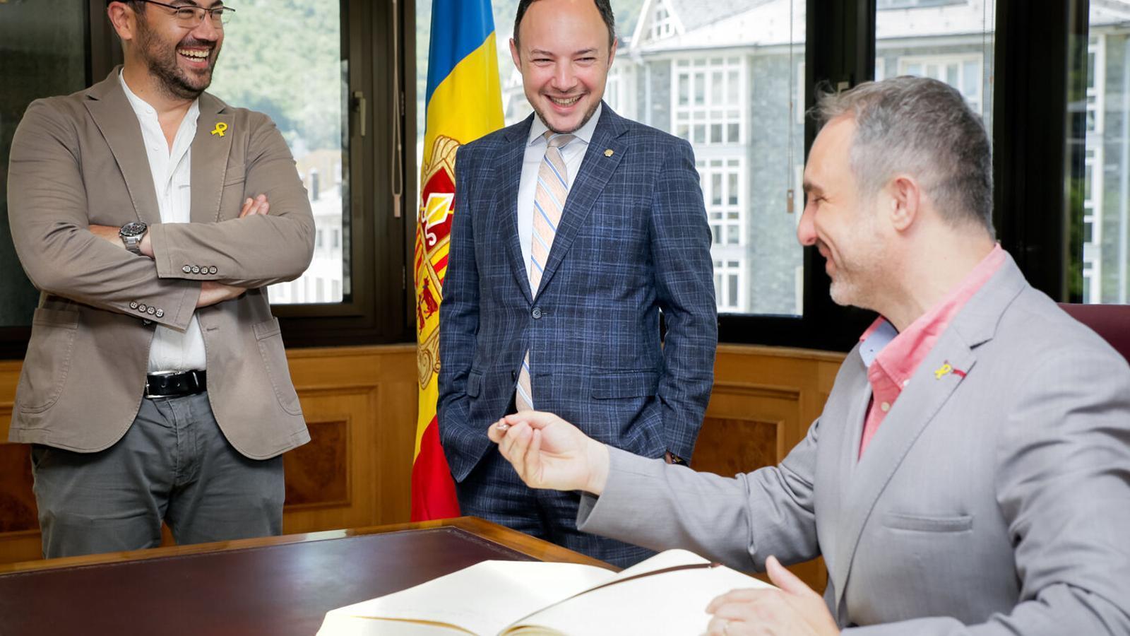 L'alcalde de la Seu d'Urgell, Jordi Fàbrega, signa el llibre d'honor amb presència del cap de Govern, Xavier Espot, i del regidor de l'ajuntament Francesc Viaplana. / SFG
