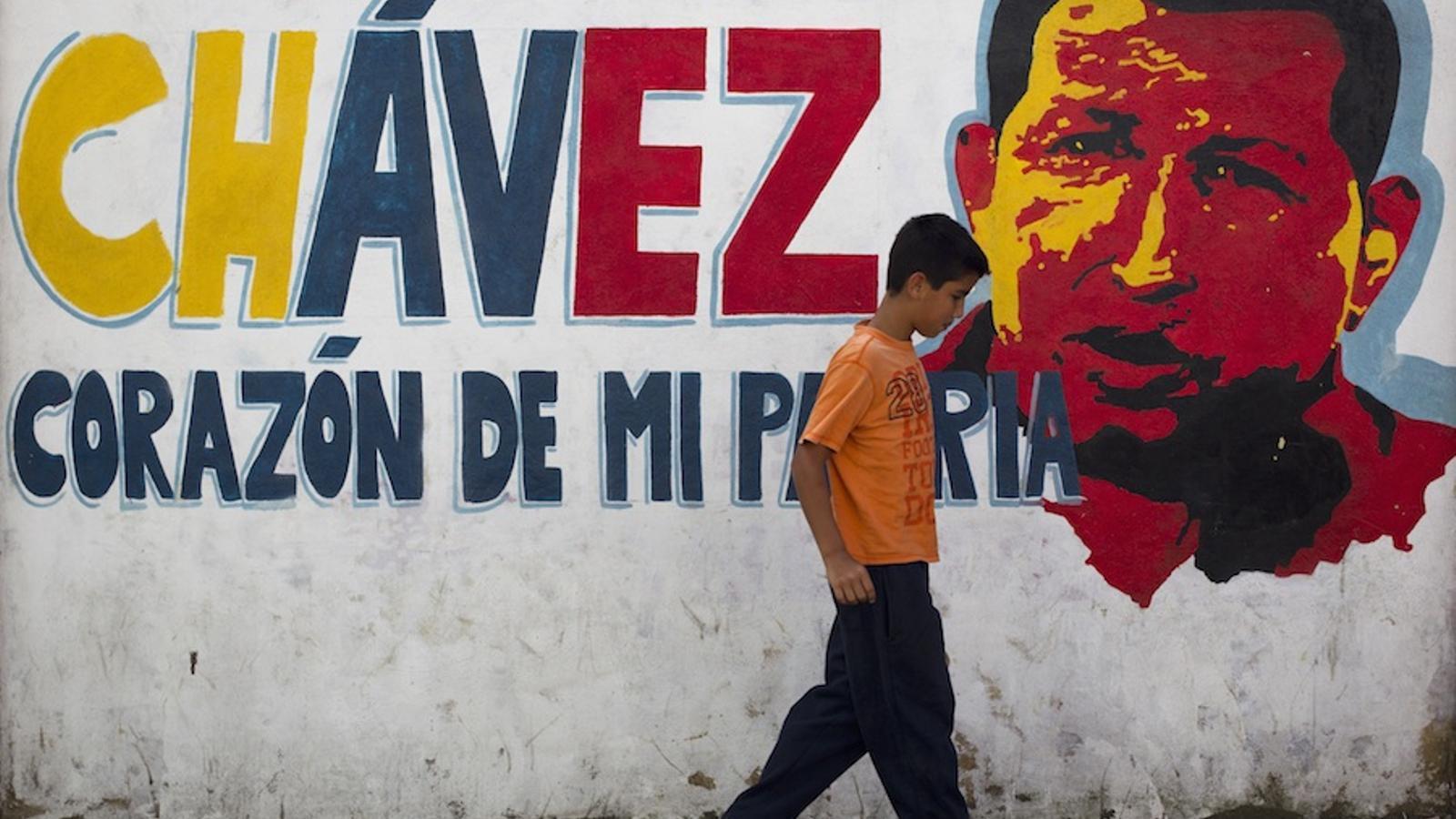 Un noi camina per davant d'un mural d'Hugo Chávez a Veneçuela / ACN
