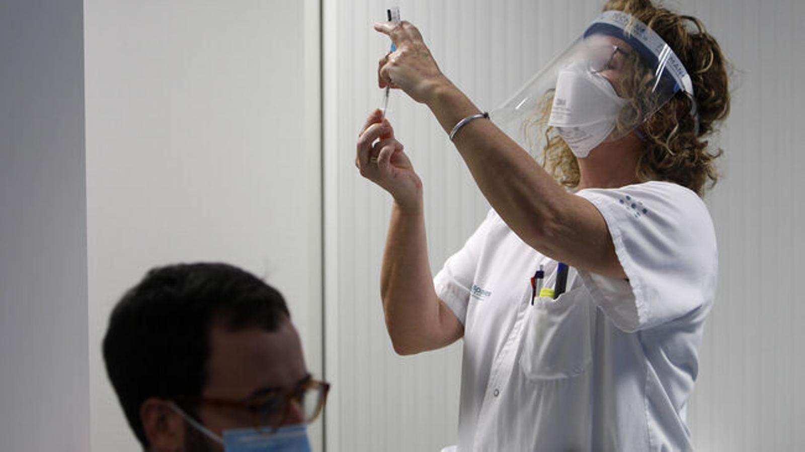 Una infermera vacunant contra el covid-19 un treballador de Son Espases. / ISAAC BUJ