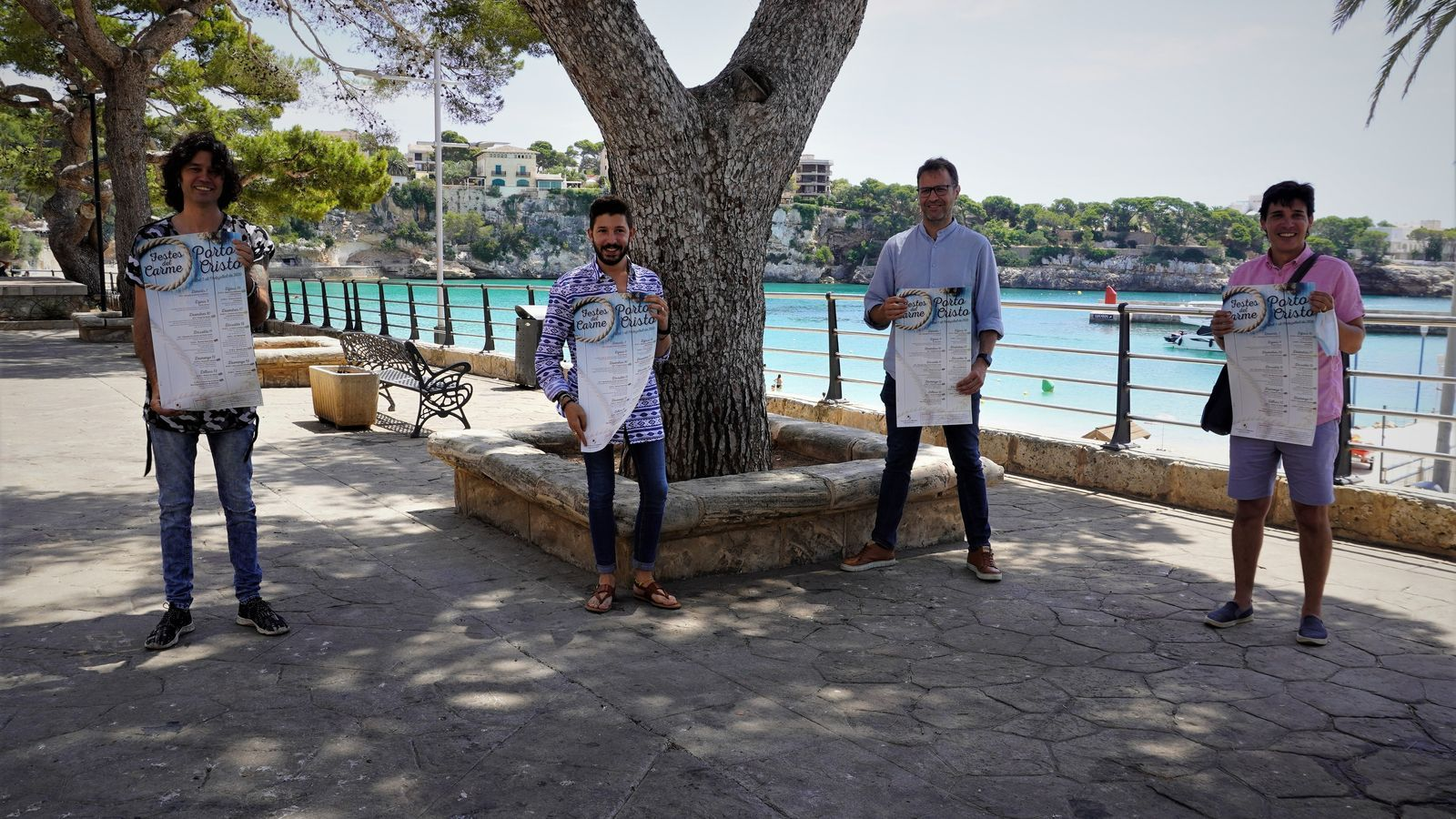 Quatre regidors de l'equip de govern presentant el cartell de festes en el passeig de la Sirena.