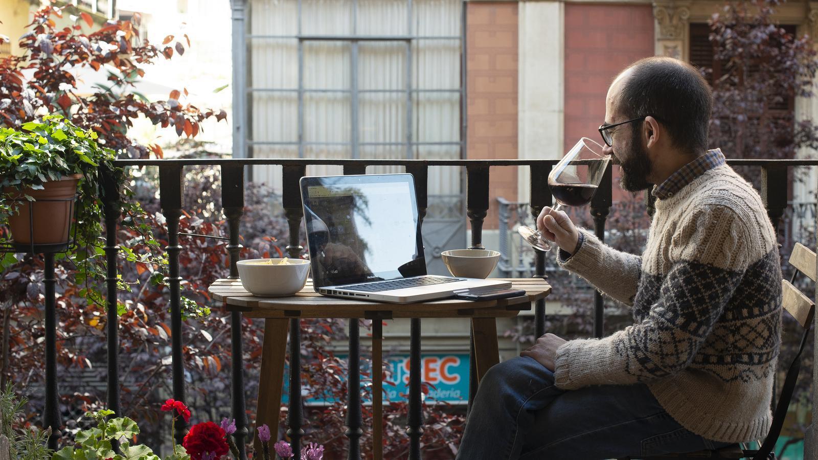 Un noi prenent una copa de vi amb un amic connectat online
