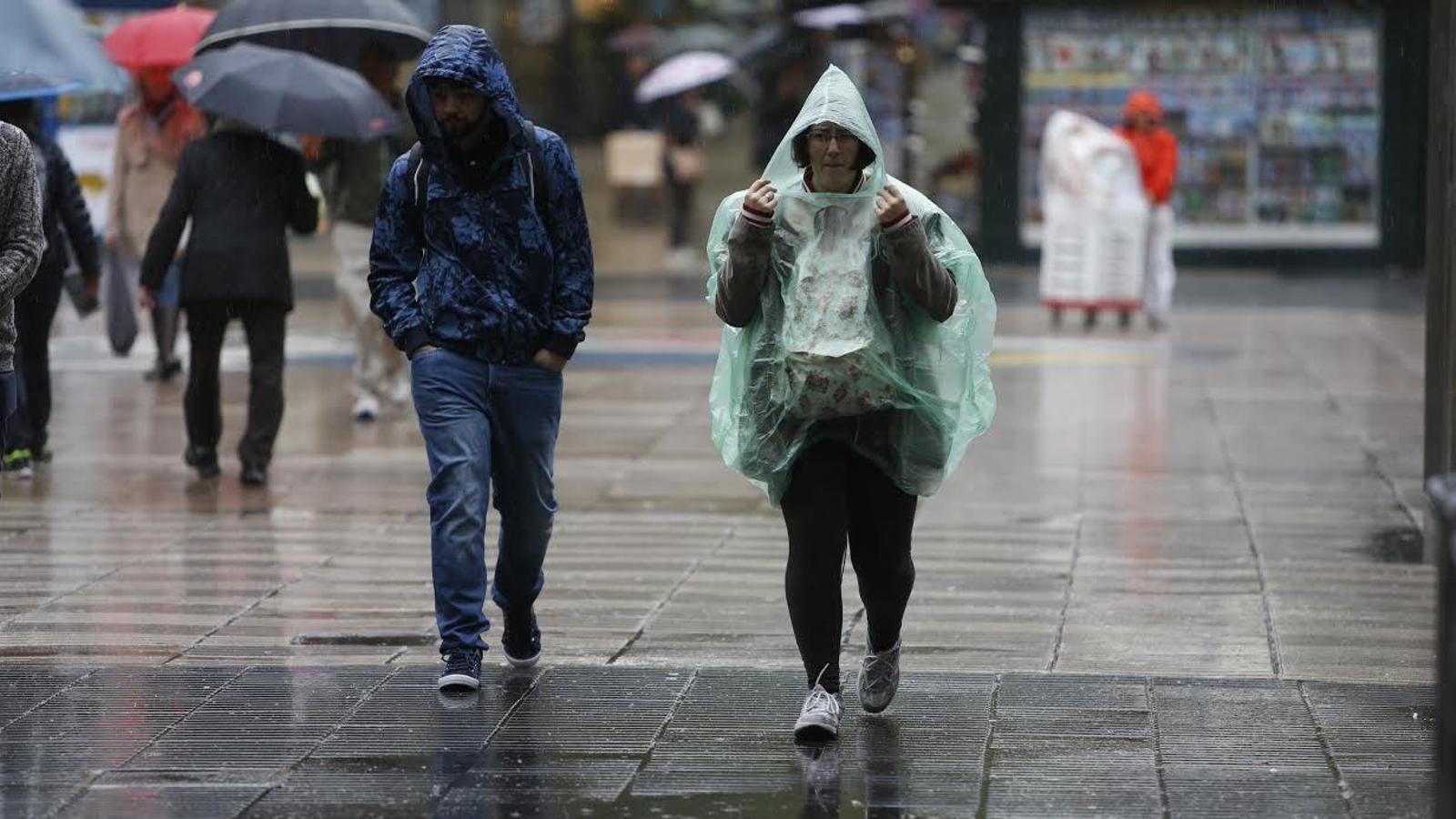 Els vianants es protegeixen de la pluja a Barcelona