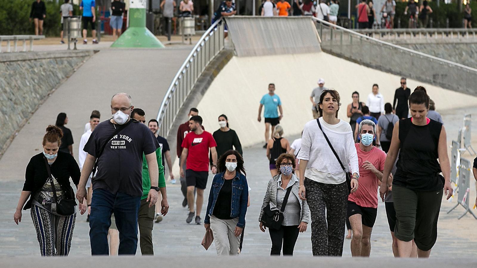 Diverses persones passejant prop de la platja del Bogatell de Barcelona amb mascareta.