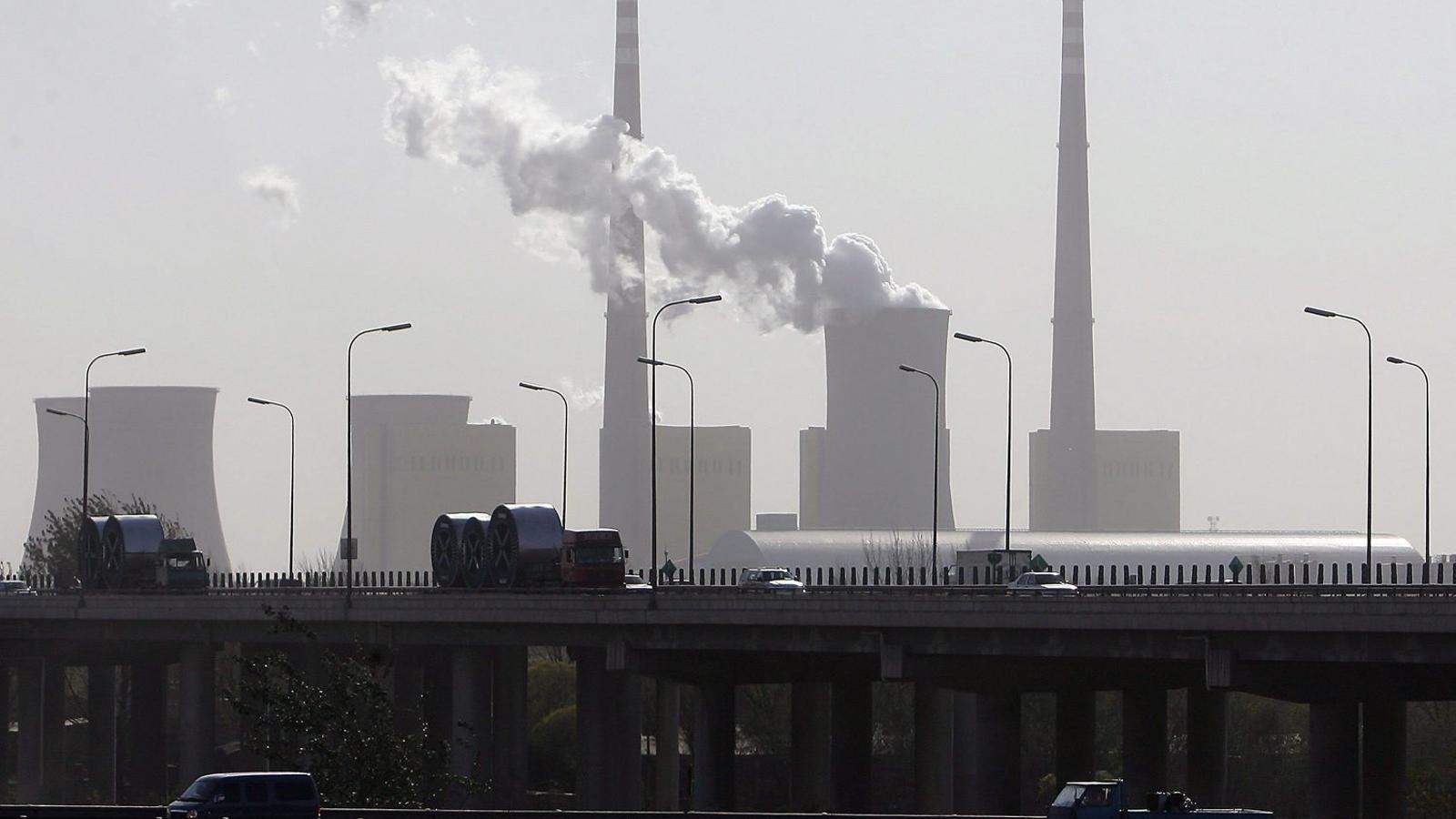 Imatge d'arxiu que mostra diversos vehicles, entre els quals dos camions, circulant pel costat d'una central elèctrica amb unes emissions evidents als afores de Pequín.