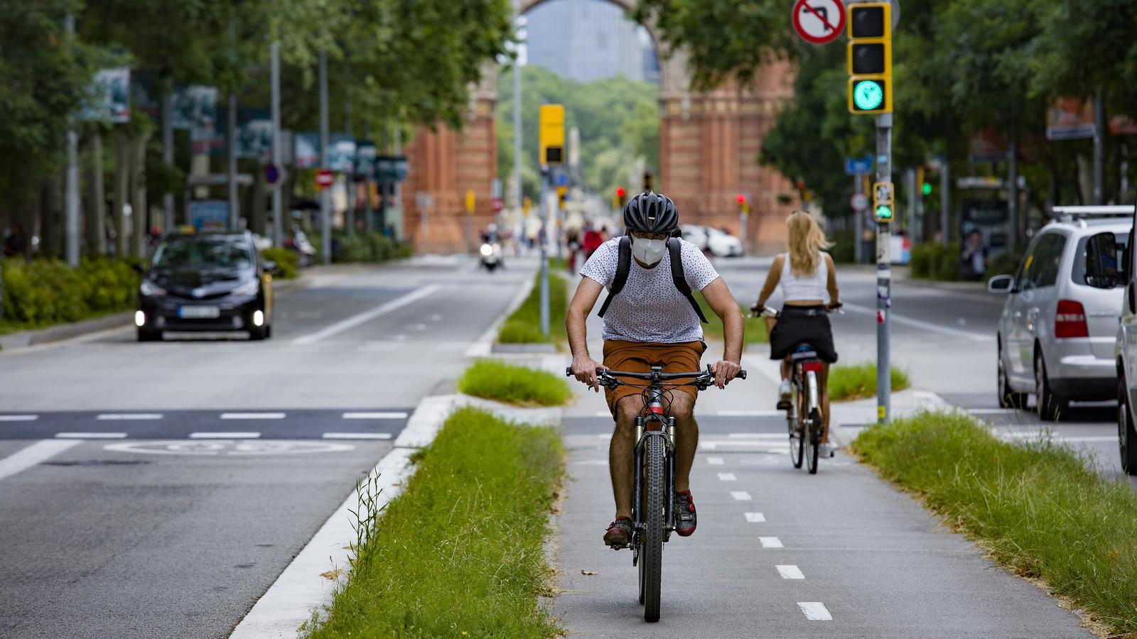 Un noi circula en bicicleta i mascareta pel Passeig Sant Joan de Barcelona